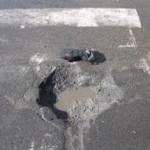 A deep pothole filled with water in middle of street is murder to your wheel rims.